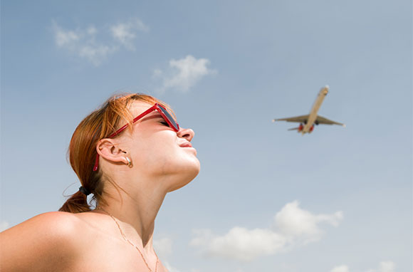 580x382_Woman-Looking-Up-at-Airplane-in-Sky