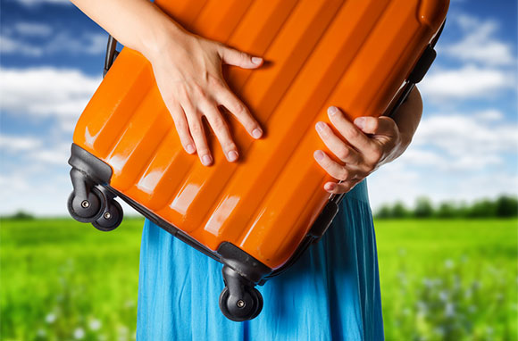 580x382_Woman-with-Orange-Suitcase-and-Country-Background