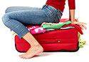 Girl-in-Jeans-and-Red-Sweater-Trying-to-Close-Bag-by-Sitting-On-It_SM