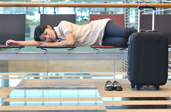 580x382_Asian-Woman-Sleeping-at-Airport