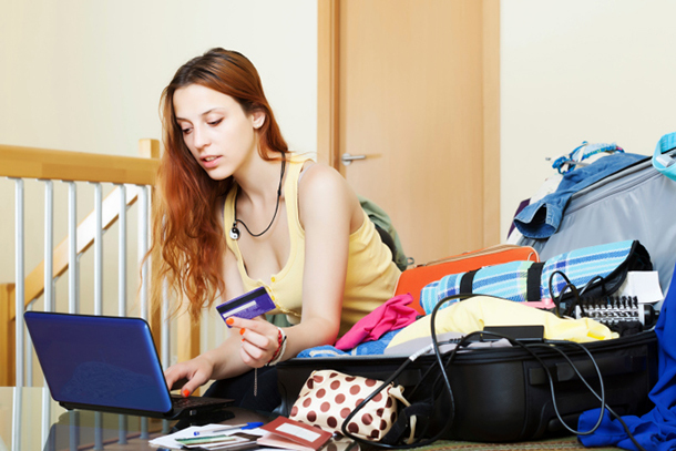 People-youngwomanusingcreditcardonlinewithfullsuitcasenexttoher-dd